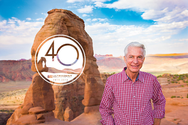 Dr. Fischer next to Arches with 40yr logo